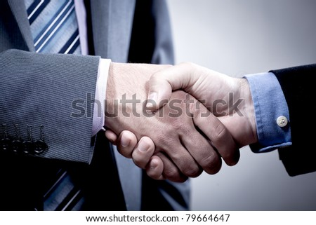 two suited men shaking hands