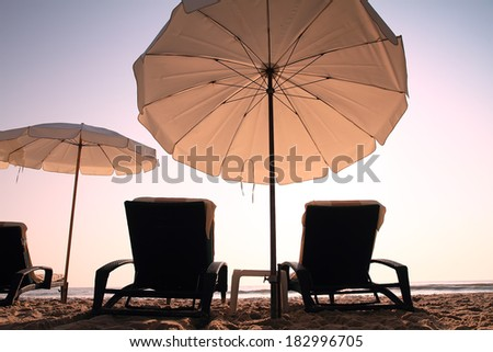 Two sun beach chairs in sunrise for relaxing