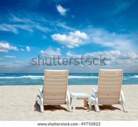 Two sun beach chairs on shore near ocean