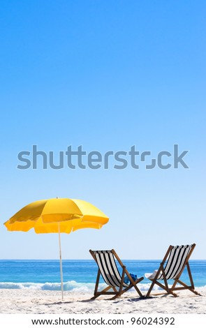 Two sun loungers and an umbrella on a perfect sunny day