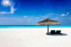 Two sunbeds under a parasol on a tropical paradise beach with blue sky, turquoise sea and copy space