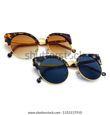 Two sunglasses with black and brown lenses on white background #1333137950