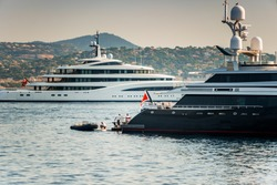 Two Super Yachts anchored in the Gulf of Staint-Tropez, one with crew and tender at the back working on deck.