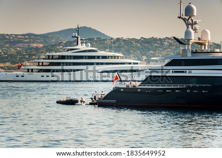 Two Super Yachts anchored in the Gulf of Staint-Tropez, one with crew and tender at the back working on deck. Stockfoto ©