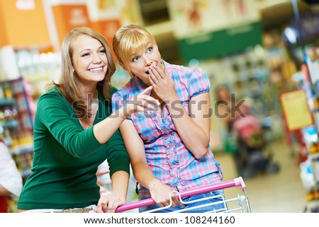 Two suprised amazed women with shopping cart at supermarket shopping mall store