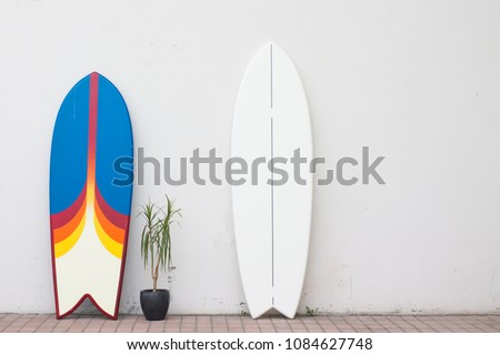 two surfboards on the street near the wall for hire rent