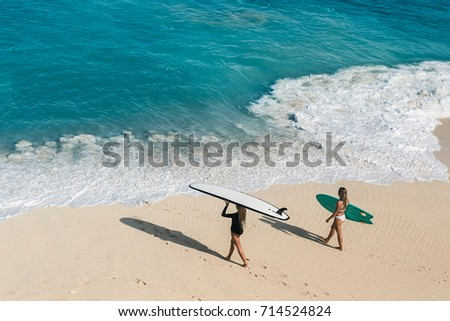 Two surfer girls in swimwear walking at beach with board in hands. Ocean at background. Summer vacation concept. Indonesia, Bali.