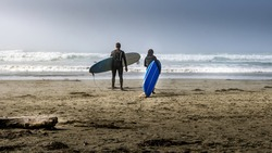 Two Surfers heading into the Fog covered Pacific Ocean at Cox Bay Beach at the Pacific Rim National Park on Vancouver Island, British Columbia, Canada