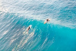 Two surfers on the wave in the ocean, top view