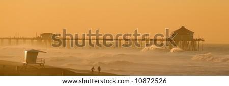 Two Surfers walk along the Beach in Huntington Beach at Dawn.