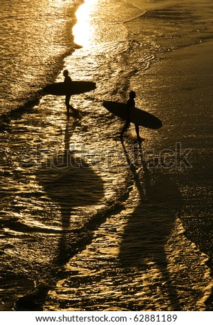 two surfers walking in silhouette on a beach.