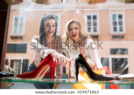 Two surpriced girl showing on elegant shoes, shopping time