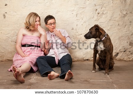 Two surprised ladies on the floor with pet dog