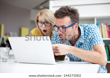 Two surprised students learning in library on laptop