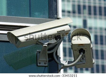 two surveillance cameras and glass - stock photo