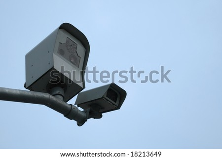 Two surveillance cameras mounted on the pole to see traffic