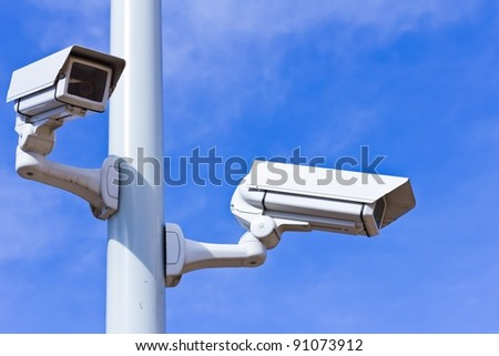Two surveillance cameras on a pole, blue sky.