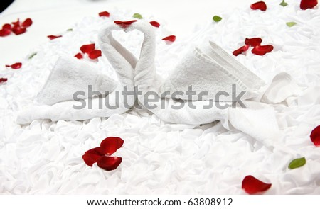 Two swans and heart made from towels on honeymoon bed.