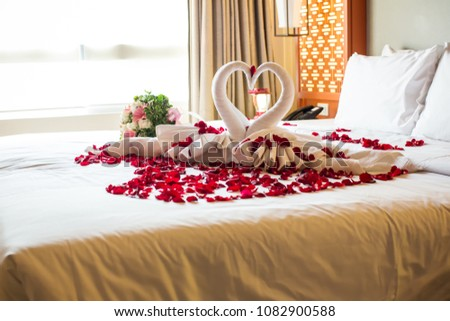 two swans made from towels are kissing on honeymoon white bed. creamy pillow and heart form, valentine signature made from red rose flower on bed decoration in bedroom.Valentine background.honey moon Foto stock ©