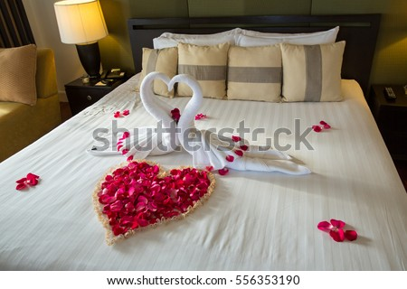 Two Swans Made From Towels Are Kissing On Honeymoon White Bed Creamy Pillow And Heart