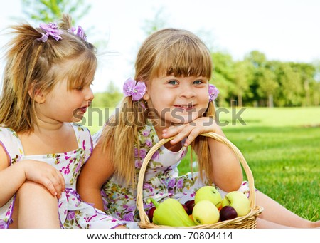 Two sweet kids in garden with fruit basket beside