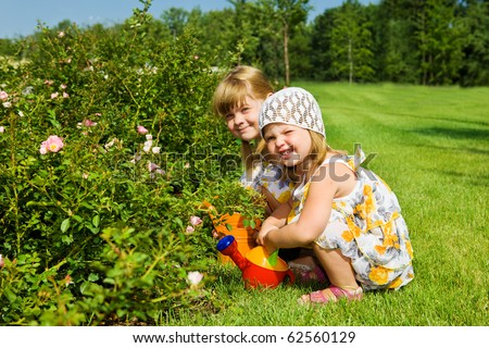 Two sweet kids watering flowers in the garden
