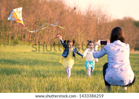 two sweet little girls running with a kite over the meadow, a mother photographing the scene with a mobile phone. Female part of the family spending time playful in the nature.  #1433386259