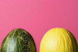 Two sweet melons on pink background. Green and yellow melons. Fresh summer fruits. Honeydew melon and frog skin melon isolated on a red background.