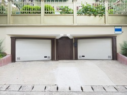 Two symmetrical garages with closed white roller shutters and an iron brown door between them