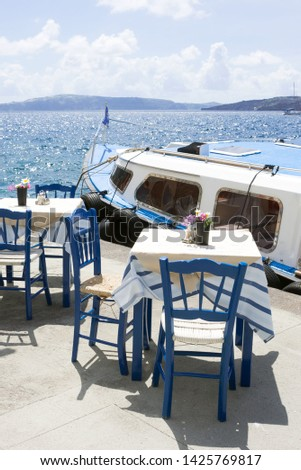 Two tables and chairs in a cozy restaurant on the embankment of the old port in the Greek city of Fira. Delicious lunch on the background of the sea and a pleasure boat. Greece, Santorini.