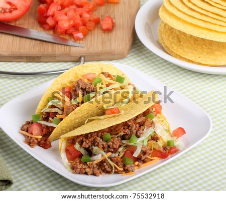 Two tacos with lettuce, tomatoes, cheese on a plate with ingredients in background