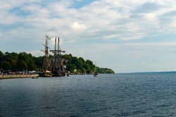 Two Tall Ships moored in a protected harbor near Brockville, Ontario on the St. Lawrence River with a treed shoreline in the background and a cloud filled blue sky