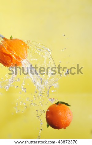 two tangerines and water splashes on yellow, close up