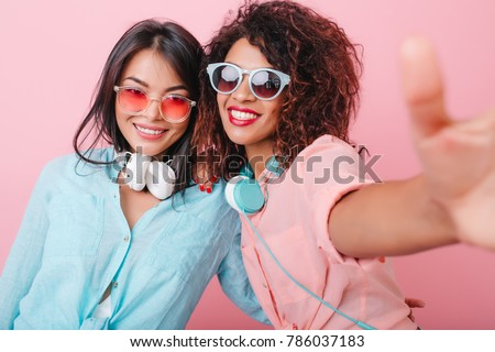 Two tanned ladies with headphones making selfie during indoor party. Enthusiastic curly woman in sunglasses taking picture of herself near romantic asian girl in blur cotton shirt.