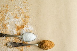 Two teaspoons of white and cane sugar on craft paper background