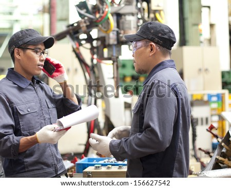 Two technician in a factory talking how repair a robot machine