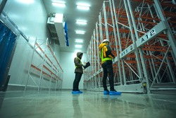 Two technician inspector check machine shelf in cold warehouse. Team professional installation shelf machine in cold storage room.