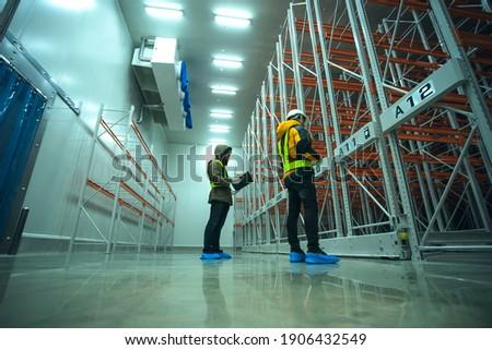 Two technician inspector check machine shelf in cold warehouse. Team professional installation shelf machine in cold storage room. Stock photo ©