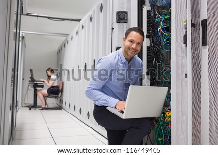 Two technicians doing data storage with their laptops