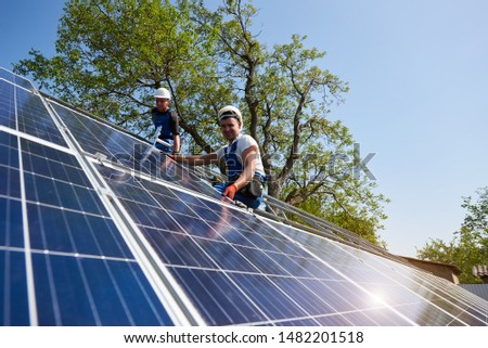Two technicians sitting on metal platform installing heavy solar photo voltaic panel on blue sky and green tree background. Stand-alone solar panel system installation and professionalism concept.
