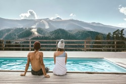 Two teen friends spending winter or spring vacation in luxury spa resort with swimming pool over alpine mountain landscape