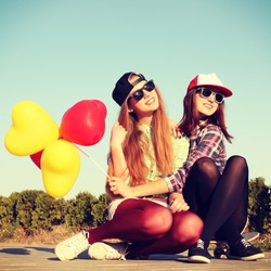 Two teen girl friends having fun together with skate board and colorful latex balloons. Outdoors, urban lifestyle. Photo toned style Instagram filters.