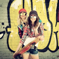 Two teen girl friends having fun together with skate board. Outdoors, urban lifestyle. Toned.