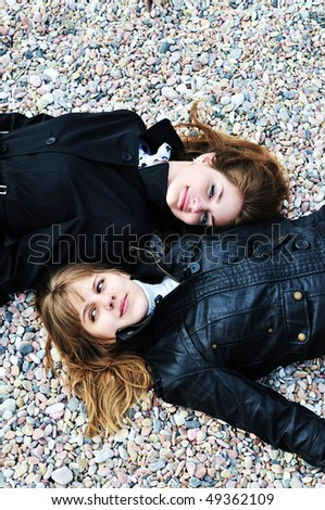 two teen girls laying on the pebble in spring time