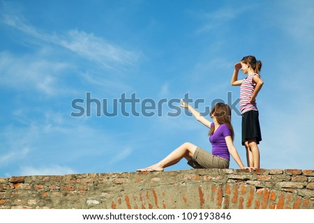 Two teen girls outdoors looking far away