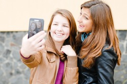 Two teen girls taking selfshot or selfy picture of themselves using tablet computer outdoors portrait