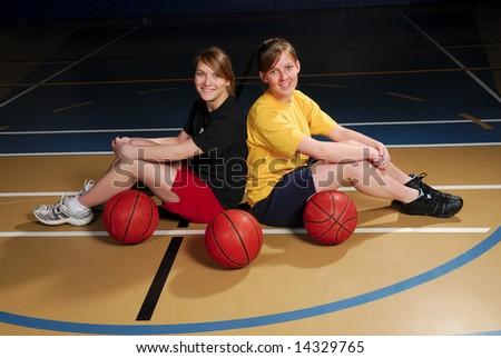 Two teenage basketball players in school gymnasium