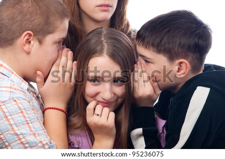 Two teenage boys and one teenage girl gossiping about their mutual friend who stands couple of feet away