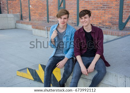 Two teenage boys brothers sitting on stairs at street talking and having fun, #673992112