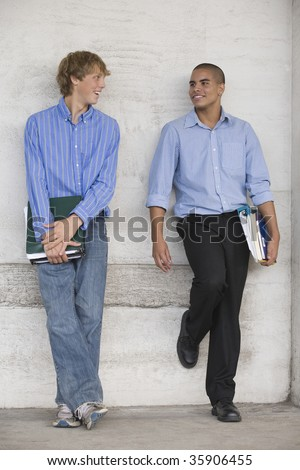 Two teenage boys holding books and talking while waiting for class.